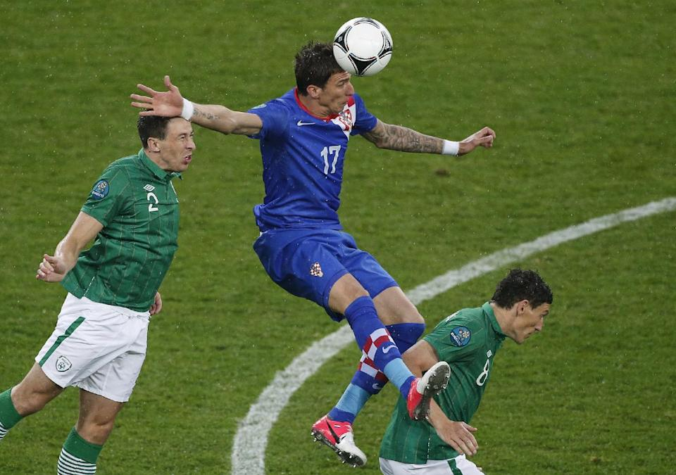 Croatia's Mario Mandzukic is flanked by Ireland's Sean St. Ledger, left, and Keith Andrews as he goes for a header during the Euro 2012 soccer championship Group C match between the Republic of Ireland and Croatia in Poznan, Poland, Sunday, June 10, 2012. (AP Photo/Anja Niedringhaus)