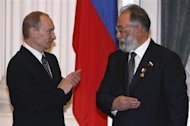 Russia&#39;s President Vladimir Putin (L) applauds after he decorated Russian State Duma member Artur Chilingarov, the leader of the 2007 Arctic deep-water expedition, with the Hero&#39;s Golden Star during a ceremony in Moscow&#39;s Kremlin in this file photo taken February 21, 2008. REUTERS/Pool
