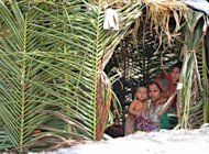 A Muslim Rohingya woman shelters with her children in Minpyar village, Rakhine state on October 28. The World Bank has approved an $80 million grant for Myanmar to support its reform drive, resuming assistance for the former pariah nation after a quarter-century absence