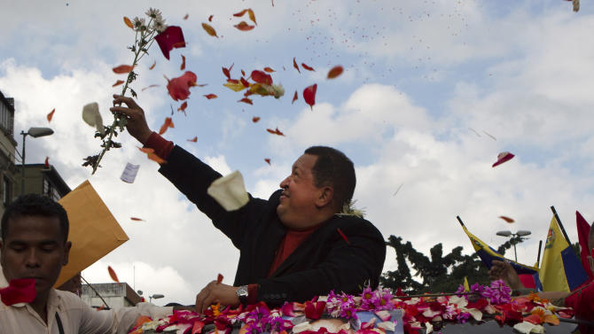 Venezuela's President Hugo Chavez catches a flower thrown by supporters during his caravan from Miraflores presidential palace to the airport in Caracas, Venezuela, Friday Feb. 24, 2012. Chavez bid an emotional goodbye to soldiers and supporters and waved to crowded streets in Caracas on his way to Cuba for urgent surgery to remove a tumor he says is probably malignant. (AP Photo/Ariana Cubillos)