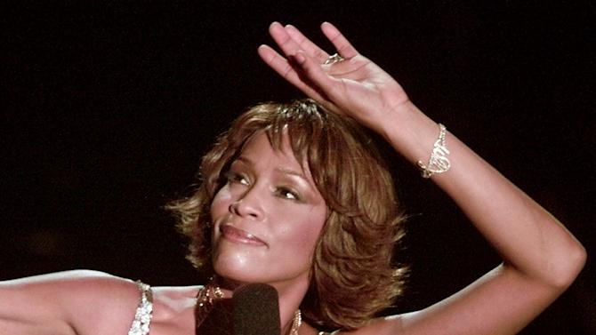 """FILE - In this April 10, 2000 file photo, entertainer Whitney Houston strikes a pose during her performance at the Shrine Auditorium in Los Angeles during taping of the """"25 Years of #1 Hits: Arista Records' Anniversary Celebration."""" Houston will be remembered on Saturday, Feb. 17, 2012,  at a funeral service at New Hope Baptist Church in Newark, N.J., the same church where a Houston sang with the choir as a young girl. While she died last Saturday in tony Beverly Hills, Calif., amid a media and celebrity crush ahead of her mentor Clive Davis' pre-Grammy party, her funeral will be a chance to reclaim Whitney Houston the person, instead of the icon. (AP Photo/Mark J.Terrill, file)"""