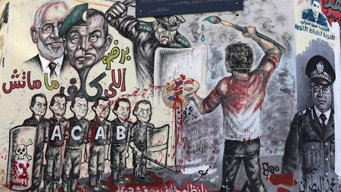 "Boys sit in front of graffiti and Arabic, bottom, that reads, ""regime you're afraid of a paint brush and a pen,"" in Tahrir Square in Cairo, Monday, Dec. 10, 2012. The Egyptian military on Monday assumed joint responsibility with the police for security and protecting state institutions until the results of a Dec. 15 constitutional referendum are announced. (AP Photo/Hassan Ammar)"