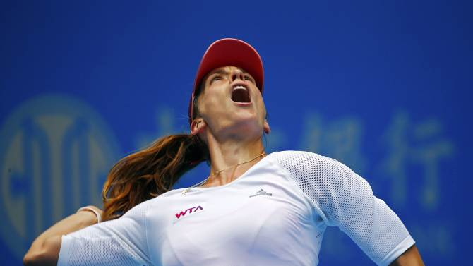 Petkovic of Germany serves during her women's singles match against Halep of Romania  at the China Open tennis tournament in Beijing