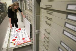Archivist Marta Crilly looks through a file drawer of posters saved from the makeshift memorial that arose following the 2013 Boston Marathon bombings at the City Archives in Boston