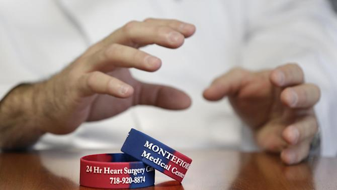 In this Thursday, Jan. 17, 2013 photo, Dr. Ricardo Bello talks to a reporter about informational bracelets for heart patients at Montefiore Medical Center in New York. Bellow, a cardiac surgeon at Montefiore Medical Center, leads a program that aims to keep patients recovering from heart surgery from having to be rehospitalized. A new study shows parts of New York have among the nation's highest readmission rates. To help, Montefiore opened a clinic last fall to check on patients' recovery a week after they go home, and patients wear a bracelet with a 24-hour phone number to call the cardiac unit at the first sign of problems. (AP Photo/Seth Wenig)