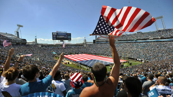 Fans cheer during a ceremony in commemoration of the 10th anniversary of the 9/11 terrorist attacks before an NFL football game between the Jacksonville Jaguars and the Tennessee Titans, Sunday, Sept. 11, 2011, in Jacksonville, Fla. (AP Photo/Stephen Morton)