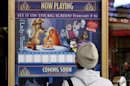 "A tourist looks at a poster for Disney's 1955 animated feature ""Lady and the Tramp"" which is currently playing at Disney's El Capitan Theatre along Hollywood Boulevard in Hollywood"