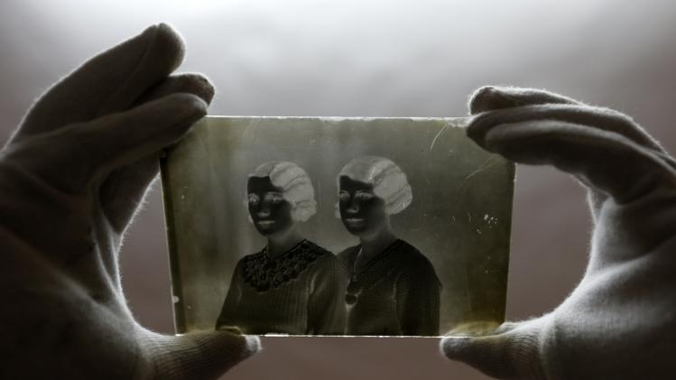 "A museographer holds a glass plate negative from the ""Costica Acsinte picture archive"" at Ialomita county museum in Slobozia"