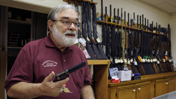 In this photo taken Wednesday, Dec. 19, 2012, gun store owner Dave Burdett talks about gun rights as he displays a hand gun in his store in College Station, Texas. Burdett, who owns an outdoors and adventure shop across the street from the sprawling Texas A&M University campus in College Station, says his affinity for guns is rooted in history, not sport. (AP Photo/Pat Sullivan)