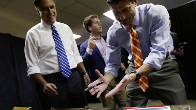 Republican vice presidential candidate Rep. Paul Ryan, R-Wis., right, jokes whether or not he should sign a photo of Republican presidential candidate and former Massachusetts Gov. Mitt Romney backstage at a campaign event at the Veterans Memorial Coliseum, Marion County Fairgrounds, in Marion, Ohio, Sunday, Oct. 28, 2012. (AP Photo/Charles Dharapak)