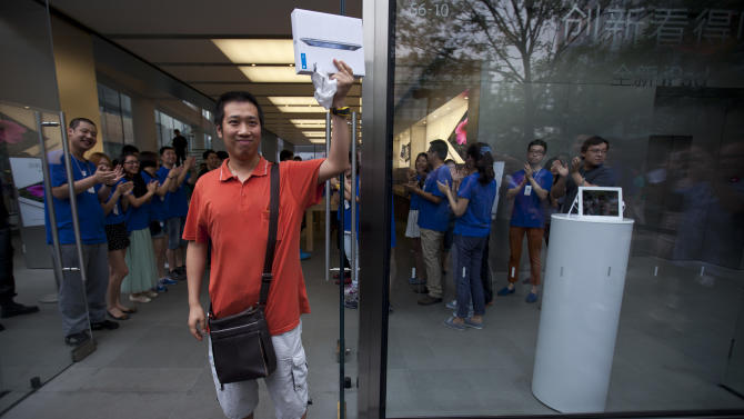A man shows his new iPad while Apple employees cheer inside its store in Beijing, China, Friday, July 20, 2012. The latest iPad has received an uneventful launch in China after Apple Inc. settled a lawsuit with a local company over ownership of the popular tablet computer's name. (AP Photo/Alexander F. Yuan)