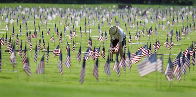 A man uprights a fallen flag at graves of military personnel and their families before Memorial Day ceremonies at Brig. General William C. Doyle Veterans Memorial Cemetery in Wrightstown N.J., Saturda