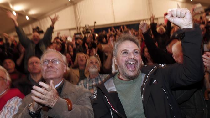 Supporters of opposition leader and head of radical leftist Syriza party Tsipras cheer at exit poll results in Athens