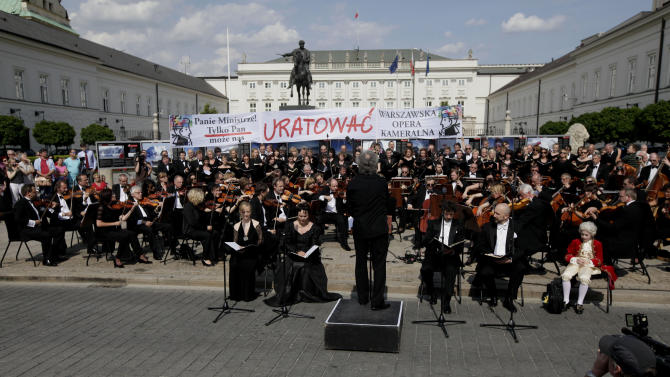 The orchestra, choir and soloists of the Chamber Opera that specializes in Mozart's music perform his Requiem, the Funeral Mass in front Presidential Palace vis a vis of the Culture Ministry in Warsaw, Poland on Tuesday, May 29, 2012 to protest recent cuts in the opera's budget and to seek government  protection. The 50-year-old opera, which  is famous for its annual festivals of all of Mozart's stage works, says it will have to close in summer if it gets no additional funds.The baner reads :  Mr. Minister only  you can save as.(AP Photo/Czarek Sokolowski)