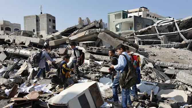 Palestinian school children walk in the rubble left days after an Israeli strike destroyed the Hamas interior ministry in Gaza City, Monday, Nov. 26, 2012. Israel launched its offensive on Nov. 14 in a bid to halt months of Palestinian rocket attacks. It says it inflicted heavy damage on Gaza militants, but the territory's armed groups fired hundreds of rockets into Israel before a cease-fire was declared Wednesday, Nov. 21, 2012.(AP Photo/Adel Hana)