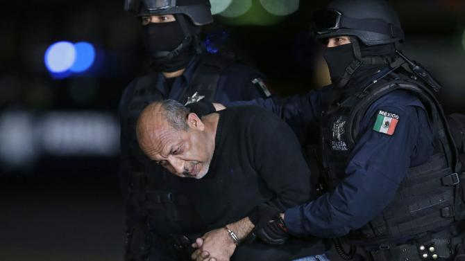 "Servando ""La Tuta"" Gomez is being escorted by police officers during a media conference about his arrest in Mexico City"