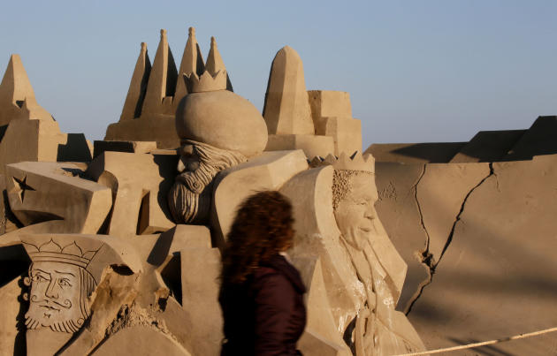 A woman walks past a nativity scene made of sand on a beach in Salou