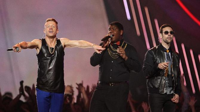 """FILE - This April 14, 2013 file photo shows Macklemore, left, and Ryan Lewis, right, performing """"Can't Hold Us"""" with Ray Dalton at the MTV Movie Awards in Sony Pictures Studio Lot in Culver City, Calif. The song was the top streamed track on Spotify from Monday, May 6, to Sunday, May 12. (Photo by Matt Sayles/Invision /AP)"""
