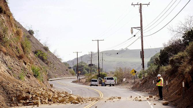 David Richardson of CalTrans photographs a rock wall where a rockslide closed Carbon Canyon Road near Carbon Canyon Regional Park in Brea, Calif., on Saturday, March 29, 2014, after an earthquake hit Orange County Friday night. More than 100 aftershocks have rattled Orange County south of Los Angeles where a magnitude-5.1 earthquake struck Friday. Despite the relatively minor damage, no injuries have been reported. (AP Photo/The Orange County Register, Ken Steinhardt) MAGS OUT; LOS ANGELES TIMES OUT