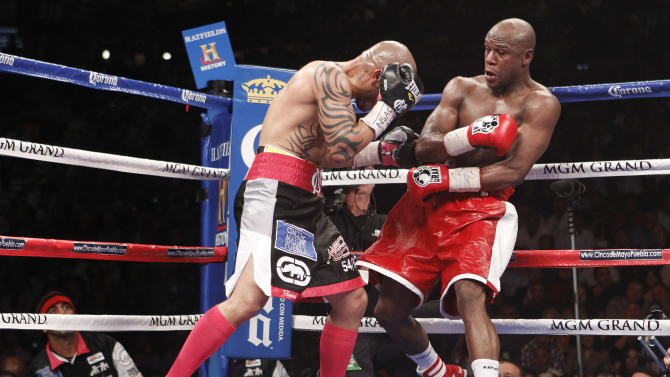 Miguel Cotto, left, throws punches against Floyd Mayweather Jr. in the fourth round during a WBA super welterweight title fight, Saturday, May 5, 2012, in Las Vegas.  (AP Photo/Eric Jamison)