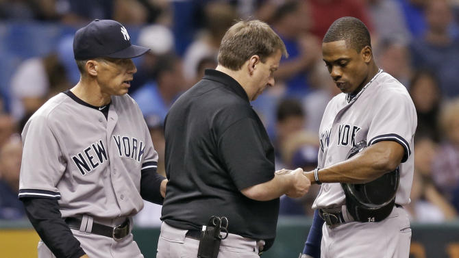 New York Yankees manager Joe Girardi, left, and a trainer, center, check Curtis Granderson's wrist during the fifth inning of a baseball game against the Tampa Bay Rays, Friday, May 24, 2013, in St. Petersburg, Fla. Granderson left the game.  (AP Photo/Chris O'Meara)