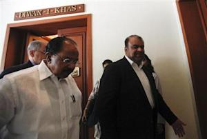 Iranian Oil Minister Qasemi walks with India's Oil Minister Moily after a meeting in New Delhi