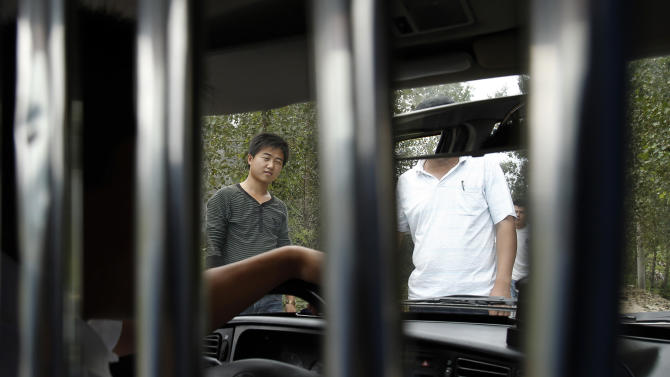 FILE - In this Sept. 9, 2010 file photo, unidentified men block a journalist's vehicle from entering Dongshigu Village where blind activist Chen Guangcheng was locked down, in eastern China's Shandong province. While China has long been a police state, controls on these non-offenders mark a new expansion of police resources at a time the authoritarian leadership is consumed with keeping its hold over a fast-changing society. (AP Photo/Andy Wong, File)