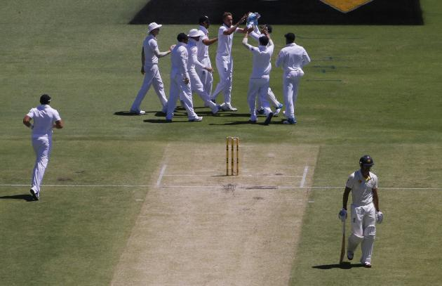 The England team celebrates after taking the wicket of Australia's Johnson as he walks off the field during the second day of the third Ashes test cricket match in Perth