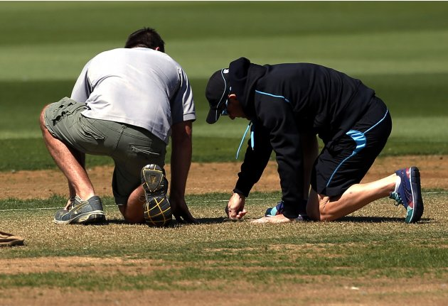 New Zealand cricket team captain McCullum inspects the pitch as he kneels down with a groundsman at a team training at the Basin Reserve in Wellington