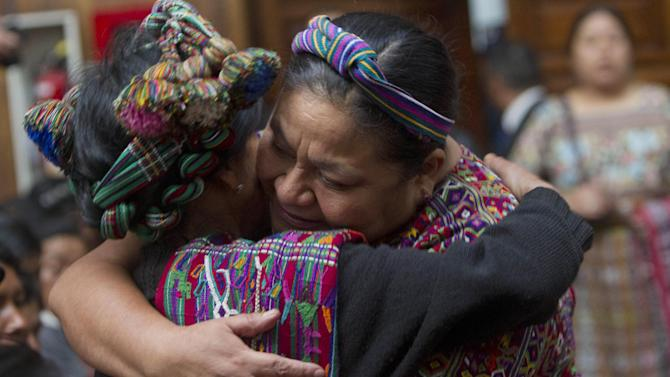 Nobel Peace Prize Laureate winner Rigoberta Menchu, right, hugs the relative of a victim of the country's civil war as they stand in court during Guatemala's former dictator Jose Efrain Rios Montt's trial on genocide charges in Guatemala City, Tuesday, March 19, 2013. Prosecutors hope to painstakingly prove through a detailed recreation of the military chain of command that Gen. Efrain Rios Montt must have had knowledge of the massacres of Mayan Indians and others in the Guatemalan highlands during one of the bloodiest phases of the country's long civil war. Because he held absolute power over the U.S.-backed military government, his failure to stop the slaughter is proof of his guilt, prosecutors and lawyers for victims say. (AP Photo/Moises Castillo)