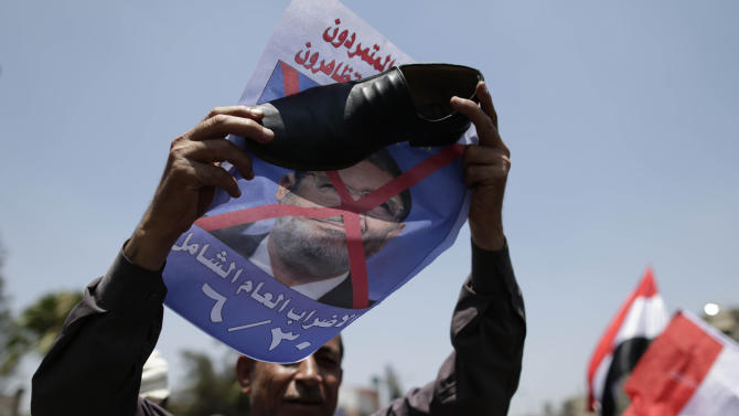 "An opponent of Egypt's Islamist President Mohammed Morsi holds a shoe against a poster with Arabic that reads, ""Huge year strike,"" during a protest outside the presidential palace in Cairo, Egypt, Sunday, June 30, 2013. Organizers of a mass protest against Morsi claimed Saturday that more than 22 million people have signed their petition demanding the Islamist leader step down, asserting that the tally was a reflection of how much the public has turned against his rule. (AP Photo/Hassan Ammar)"