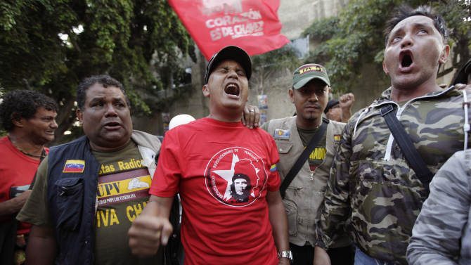 """Supporters of Venezuela's President Hugo Chavez yell """"Long Live Chavez!"""" and sing their nation's anthem after learning that Chavez has died through an announcement by the vice president in Caracas, Venezuela, Tuesday, March 5, 2013. Venezuela's Vice President Nicolas Maduro announced that Chavez died on Tuesday at age 58 after a nearly two-year bout with cancer. During more than 14 years in office, Chavez routinely challenged the status quo at home and internationally. He polarized Venezuelans with his confrontational and domineering style, yet was also a masterful communicator and strategist who tapped into Venezuelan nationalism to win broad support, particularly among the poor. (AP Photo/Ariana Cubillos)"""