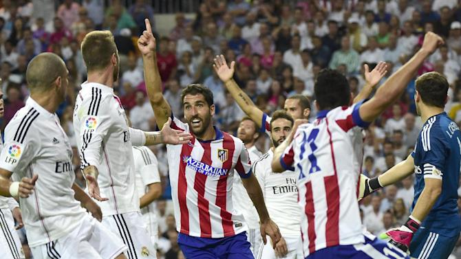Atletico Madrid's midfielder Raul Garcia (C) celebrates after scoring during the Spanish Supercup first-leg football match Real Madrid CF vs Club Atletico de Madrid at the Santiago Bernabeu stadium in Madrid on August 19, 2014