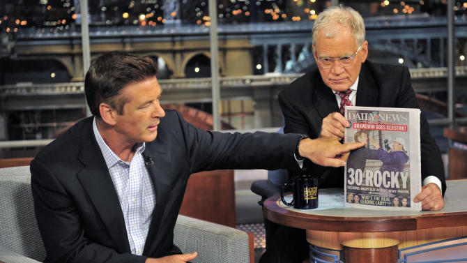 In this photo provided by CBS Entertainment, David Letterman holds a copy of the Daily News as guest Alec Baldwin gestures to the front page showing a photo of his June 6th confrontation with a photographer, during his appearance on the Late Show with David Letterman, in New York, Wednesday, June 20, 2012. (AP Photo/CBS Entertainment, John Paul Filo)