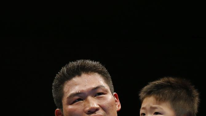 Miura of Japan holds his son Takeharu as he celebrates his victory over Puerta of Mexico during their WBC boxing super featherweight title bout in Tokyo