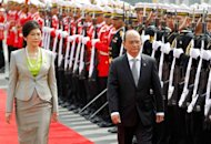 Myanmar President Thein Sein (R) and Thai Prime Minister Yingluck Shinawatra (L) review the honor guard during a welcoming ceremony at Government House in Bangkok. Thailand and Myanmar pledged on Monday to press ahead with a multi-billion-dollar deep sea port project and to open new border crossings during summit talks focused on strengthening economic ties