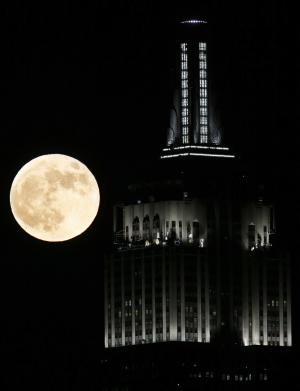A full moon rises near the Empire State Building, as seen from Hoboken, N.J., Wednesday, Nov. 28, 2012. (AP Photo/Julio Cortez)