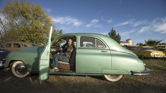 """In this photo taken Monday, Jan. 7, 2013, car collector Chuck Shubb, 72, from Los Angeles, poses with his 1948 Packard Super 8 Touring Sedan, one of several cars featured in the film, """"Gangster Squad,"""" in Los Angeles. To bring the story of mobster Mickey Cohen's reign over post-war Los Angeles to life, the director of """"Gangster Squad"""" employed Sean Penn, Josh Brolin, Ryan Gosling and more than 100 irreplaceable vintage American cars. (AP Photo/Damian Dovarganes)"""