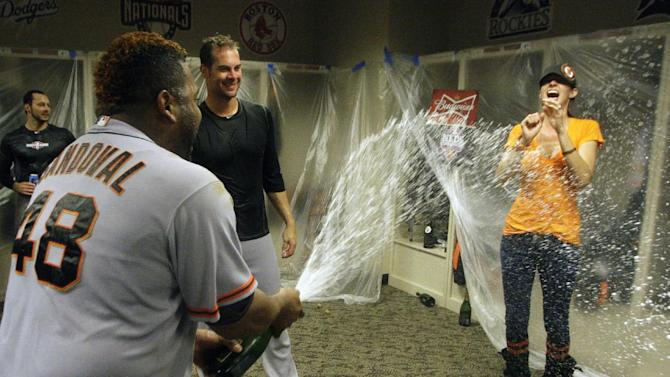 San Francisco Giants' Pablo Sandoval (48) sprays Nicole Vogelsong, wife of Giants pitcher Ryan Vogelsong, in the locker room after the Giants defeated the Cincinnati Reds 6-4 in Game 5 of the National League division baseball series, Thursday, Oct. 11, 2012, in Cincinnati.  The Giants won the final three games, all in Cincinnati, and advanced to the NL championship series.  (AP Photo/David Kohl)