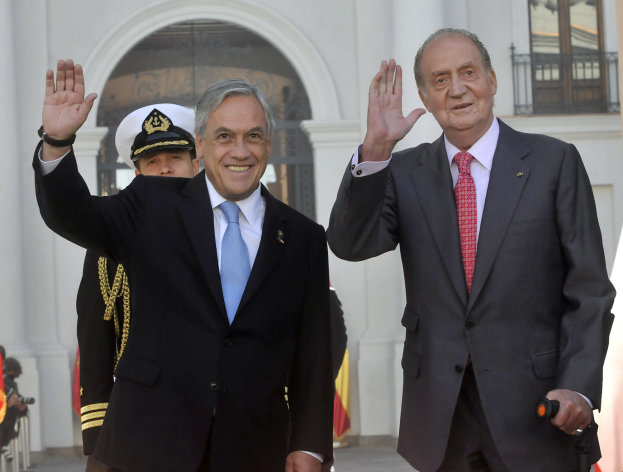 In this picture released by Chile's Presidential Press Office, Chile's President Sebastian Pinera and Spain's King Juan Carlos wave during a welcome ceremony at La Moneda presidential palace in Santiago, Chile, Tuesday, June 5, 2012. (AP Photo/Chile's Presidential Press Office, Luis Manuel de la Maza)