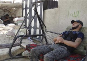 A Free Syrian Army fighter rests as a fellow fighter…