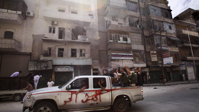 """In this Tuesday, Sept. 11, 2012 photo, Syrian rebel fighters flash the victory sign while moving past a building destroyed partly in a government shelling in Aleppo, Syria. Arabic reads on the vehicle, """"Free army"""". Rebels have taken a major stride in uniting their ranks in the battle for Syria's largest city, giving them hope they could tip the balance in three-months of bloody stalemate in Aleppo, one of the biggest prizes of the civil war. The question is how much more destruction the city can bear. Regime troops are retaliating with heavier bombardment, and civilians are bearing the brunt, their neighborhoods left in rubble. (AP Photo/Muhammed Muheisen)"""