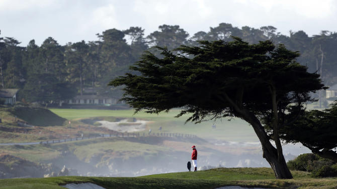 A marshal looks out onto the 13th green of the Monterey Peninsula Country Club Shore Course during the second round of the AT&T Pebble Beach Pro-Am golf tournament on Friday, Feb. 8, 2013, in Pebble Beach, Calif. (AP Photo/Eric Risberg)