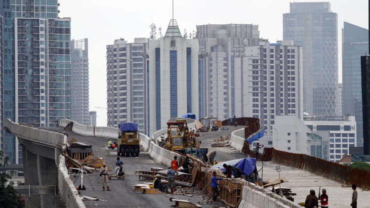 In this Friday, Jan. 11, 2013 photo, workers build an elevated highway in Jakarta, Indonesia. Months behind schedule, the construction crew racing to finish a highway encircling Indonesia's traffic-choked capital is being blocked by a determined group of locals and the ramshackle cemetery that is home to their ancestors. (AP Photo/Achmad Ibrahim)