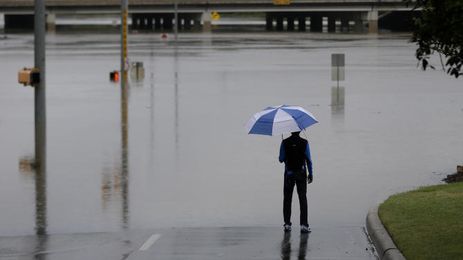 A man surveys floodwaters caused by heavy rains, Saturday, May 25, 2013, in San Antonio. (AP Photo/Eric Gay)
