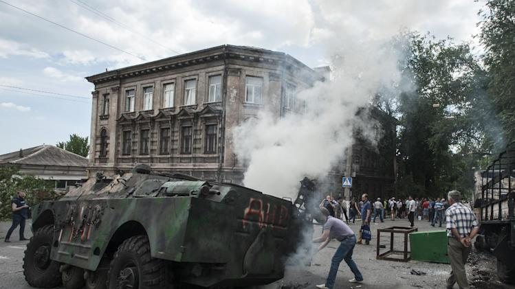 Local citizens gather around a burning military vehicle at a site of a battle between Ukrainian troops and pro-Russian fighters in Mariupol, eastern Ukraine, Friday, June 13, 2014. Ukraine's interior minister says that government troops have attacked pro-Russian separatists in the southern port of Mariupol. Arsen Avakov said Friday that four government troops were wounded as forces retook buildings occupied by the rebels in the center of the town. (AP Photo/Evgeniy Maloletka)