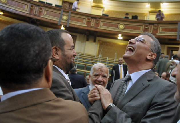 Egyptian lawmakers greet each other at a brief session of Parliament, the first since the country&#39;s high court ruled the chamber unconstitutional, in Cairo, Egypt, Tuesday, July 10, 2012. Egypt&#39;s Islamist-dominated parliament convened Tuesday in defiance of a ruling by the country&#39;s highest court and swiftly voted to seek a legal opinion on the decision that invalidated the chamber over apparent election irregularities. (AP Photo)
