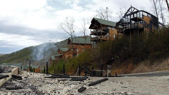 The remains of cabins at the Black Bear Ridge Resort can be seen, Monday, March 18, 2013 where a fire destroyed or damaged 65 structures and charred 165 acres between Pigeon Forge and the Wears Valley area of Sevier County, Tenn. by noon on Monday, March 18, 2013. The fire was reported on Sunday afternoon. The area in the foreground is where the fire started. (AP Photo/Wade Payne)