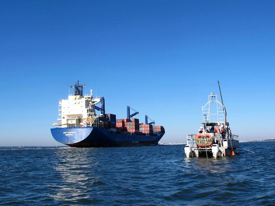 A  container ship moves into the harbor in Charleston, S.C., on Friday, Nov. 9, 2012, passing a boat taking sediment samples of the harbor floor. The samples are required for a study of a $300 million deepening of the harbor shipping channel so it can handle larger container ships. (AP Photo/Bruce Smith).