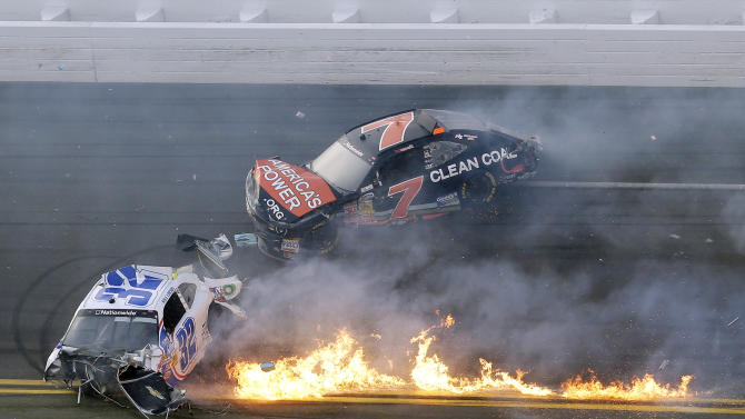 Kyle Larson's car is on fire as he slides down the track with Regan Smith after being involved in a crash at the conclusion of the NASCAR Nationwide Series auto race Saturday, Feb. 23, 2013, at Daytona International Speedway in Daytona Beach, Fla. Larson's car hit the safety fence sending car parts and other debris flying into the stands injuring spectators. (AP Photo/Chris O'Meara)